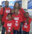 Mother and father figure with four children all wearing the same red shirt that says Maat Crew.